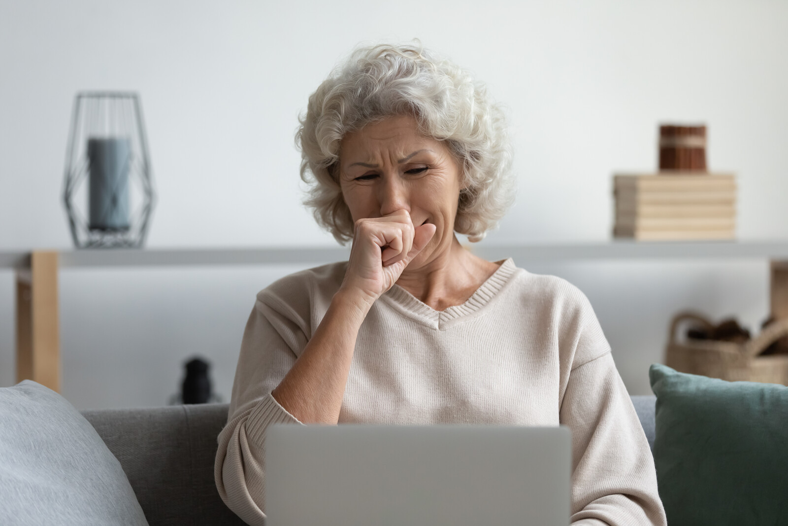 Depressed senior older woman sitting on her couch crying, looking at computer screen