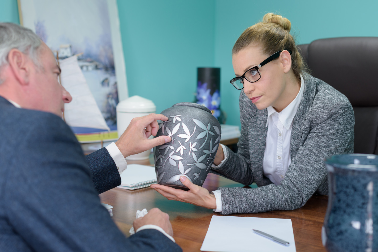 Funeral director showing an elderly man an urn as they sit at her desk