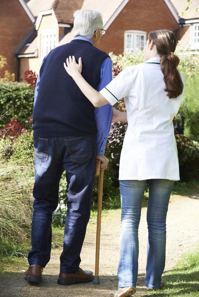 A senior man walks with a caregiver.