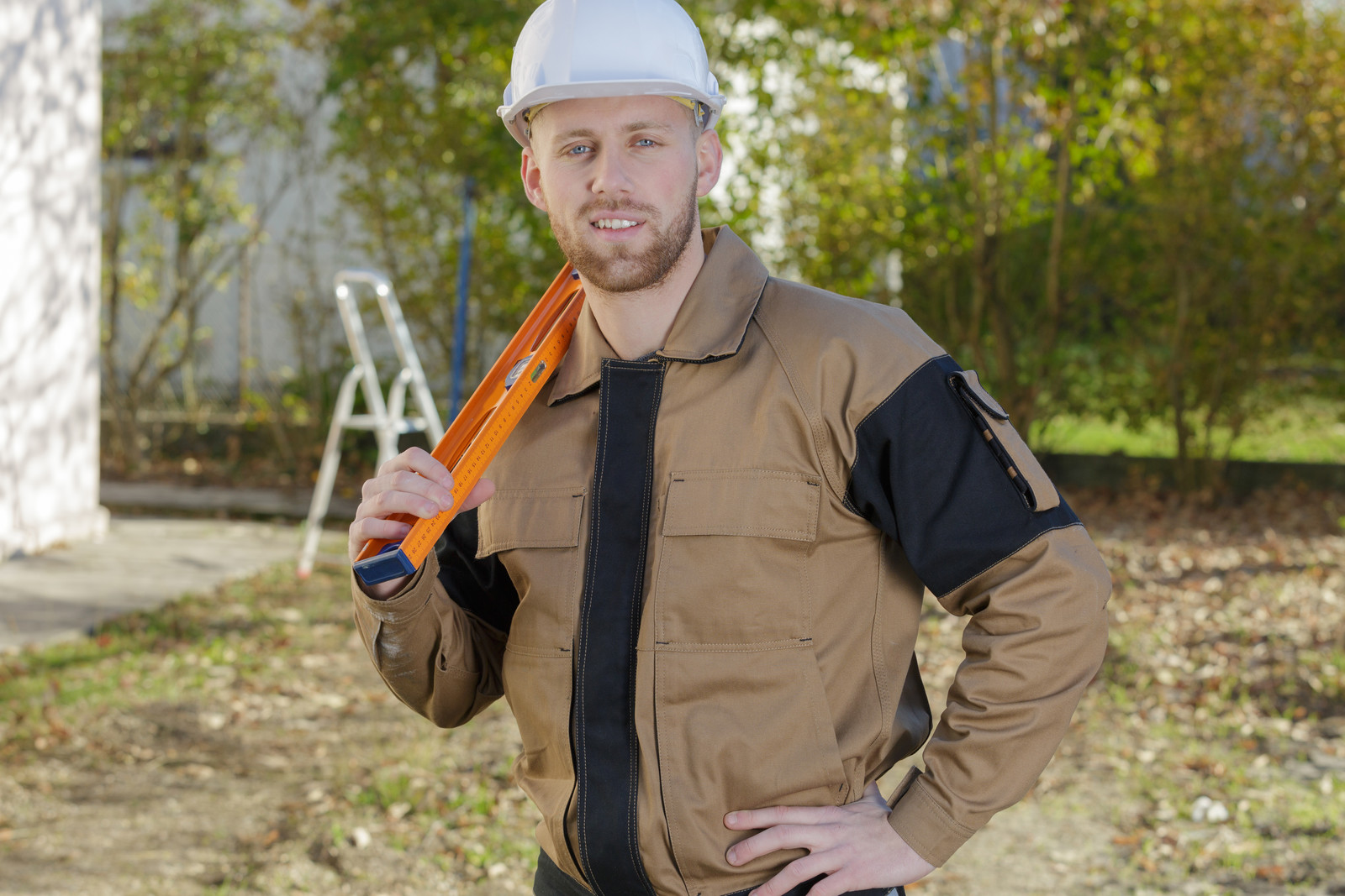 Friendly smiling home inspector holding a level standing in a yard with shrubs and buildings in the background