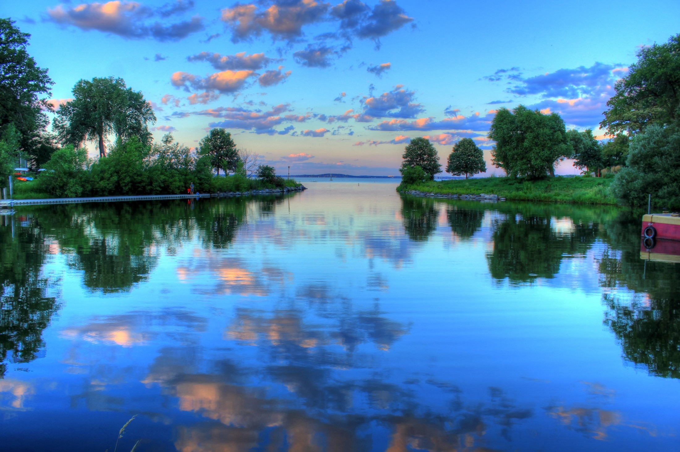 Lake Geneva with still waters reflecting the sky, trees and dig lining the lakeshore
