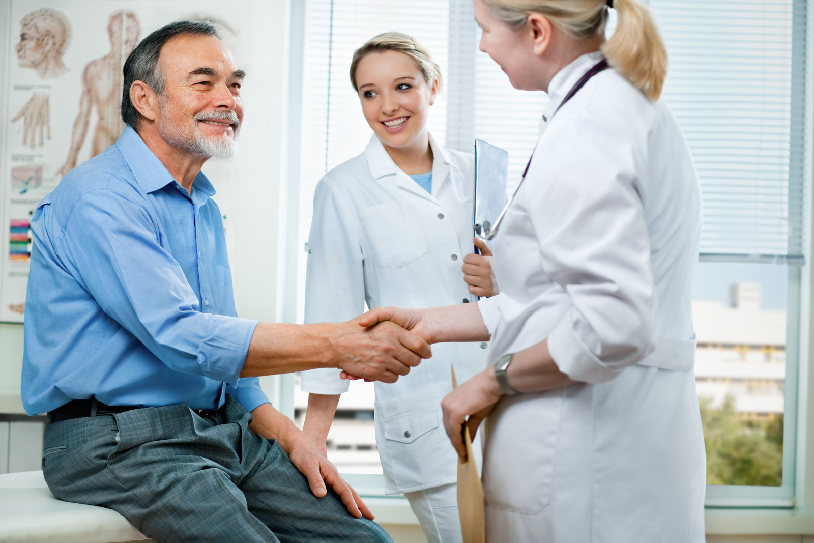 Senior man smiling and shaking hands with a female doctor sitting in an exam room.