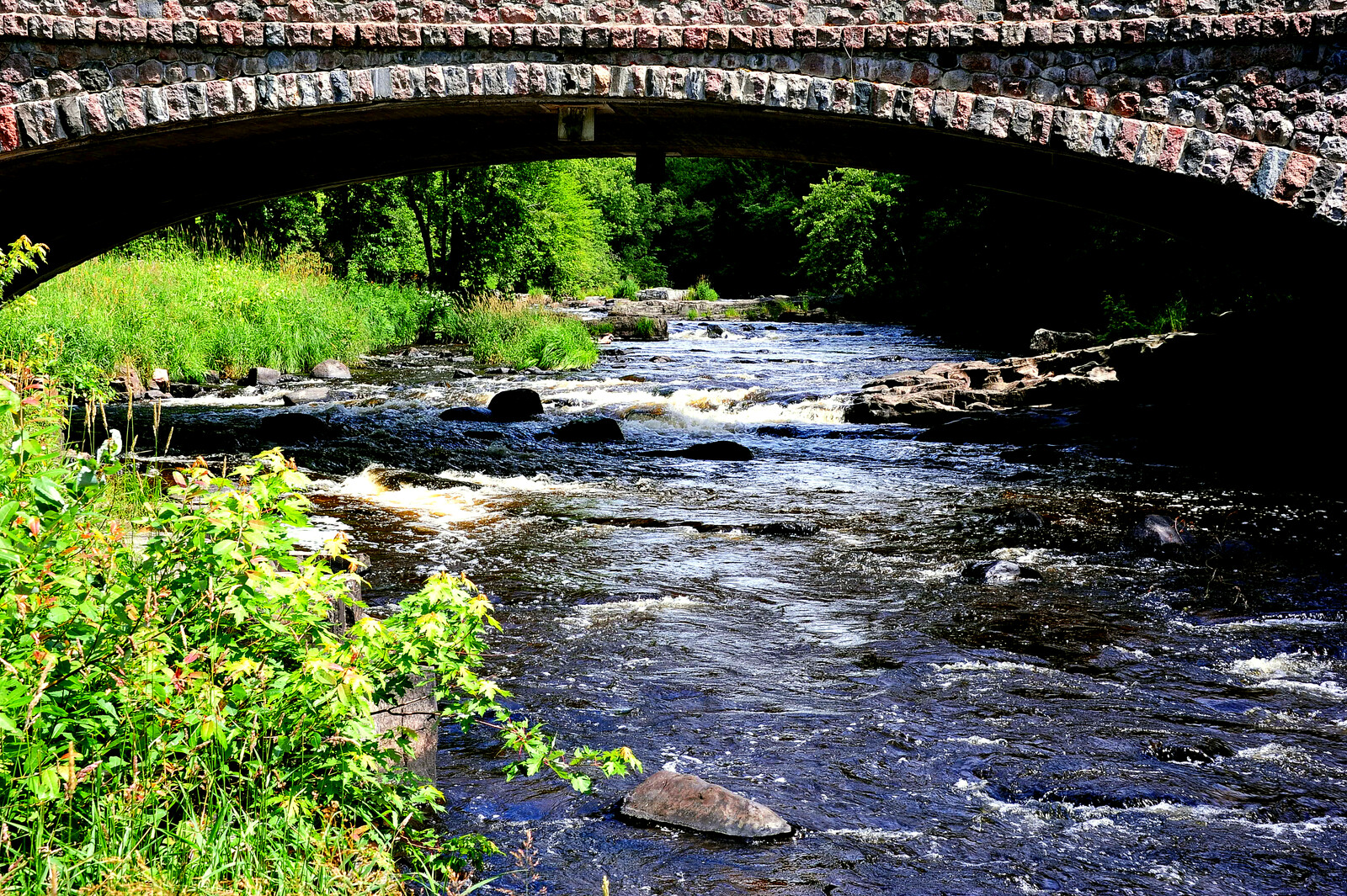 A stone bridge running over a river with greenery on the sides of the river, in Eau Claire Wisconsin