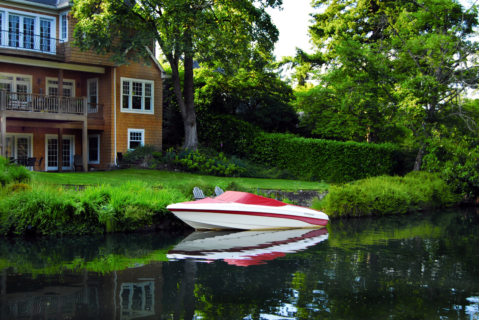 A home on Lake Oswego with a red and white boat docked out front.  With green well manicured lawns and mature trees surrounding the property
