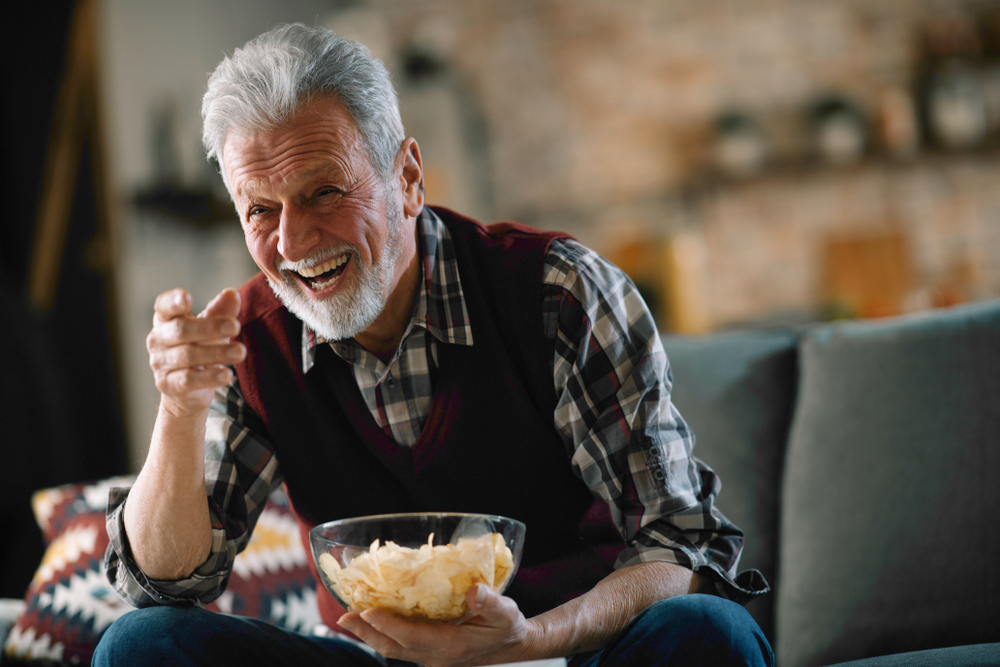 An older gentleman with a bowl of snacks laughing and watching tv