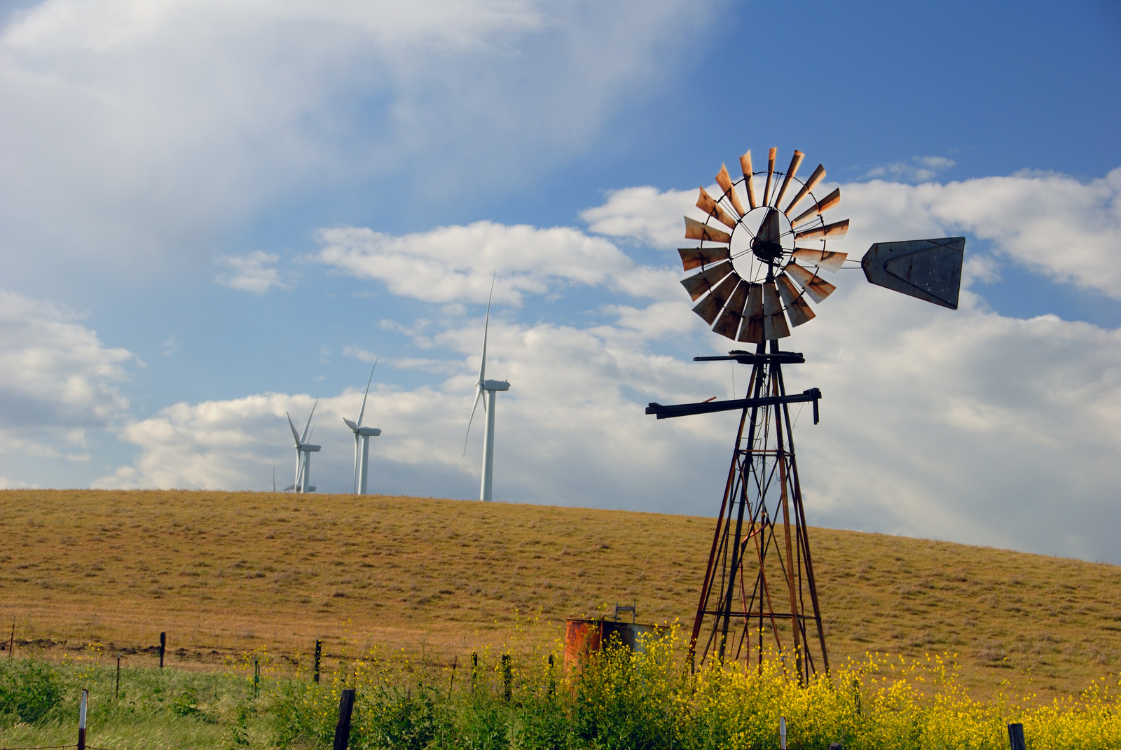 Older style ranch windmill set against new electrical power generating windmills, in the fields of rio vista, california