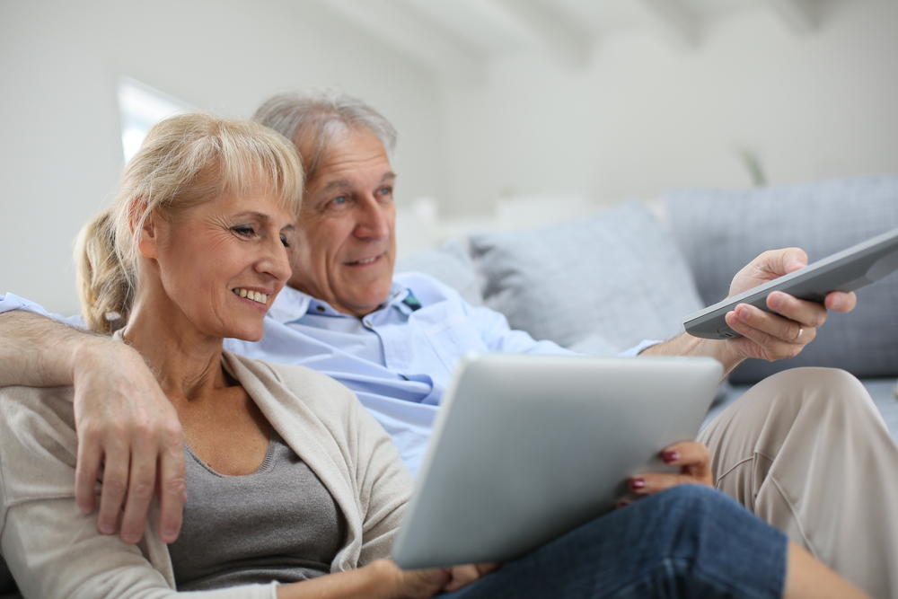 A senior couple relaxing with a TV remote and a tablet