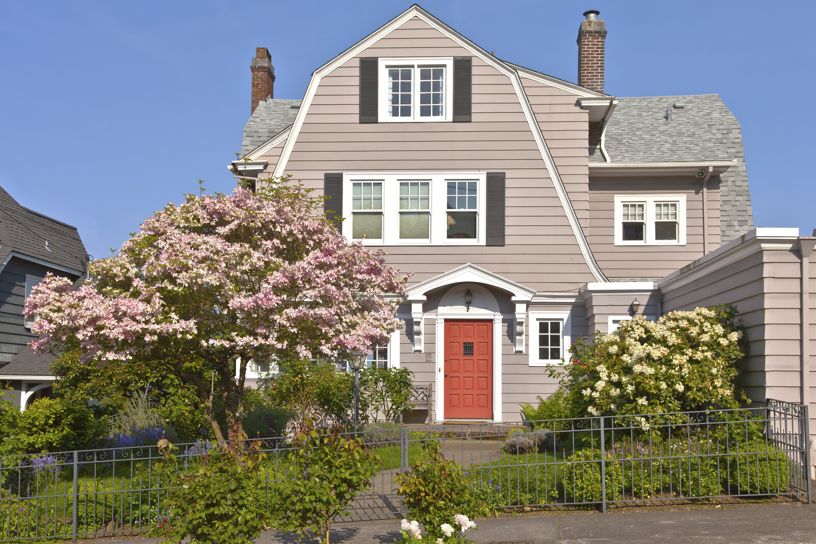 Residential barn style home with black iron fence and red door.  Shrubs and crab apple tree in the front yard
