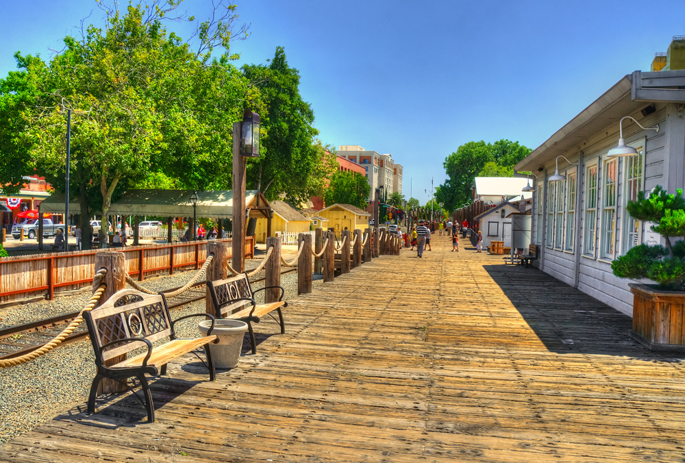 A boardwalk with benches, houses, and trees in Sacramento California