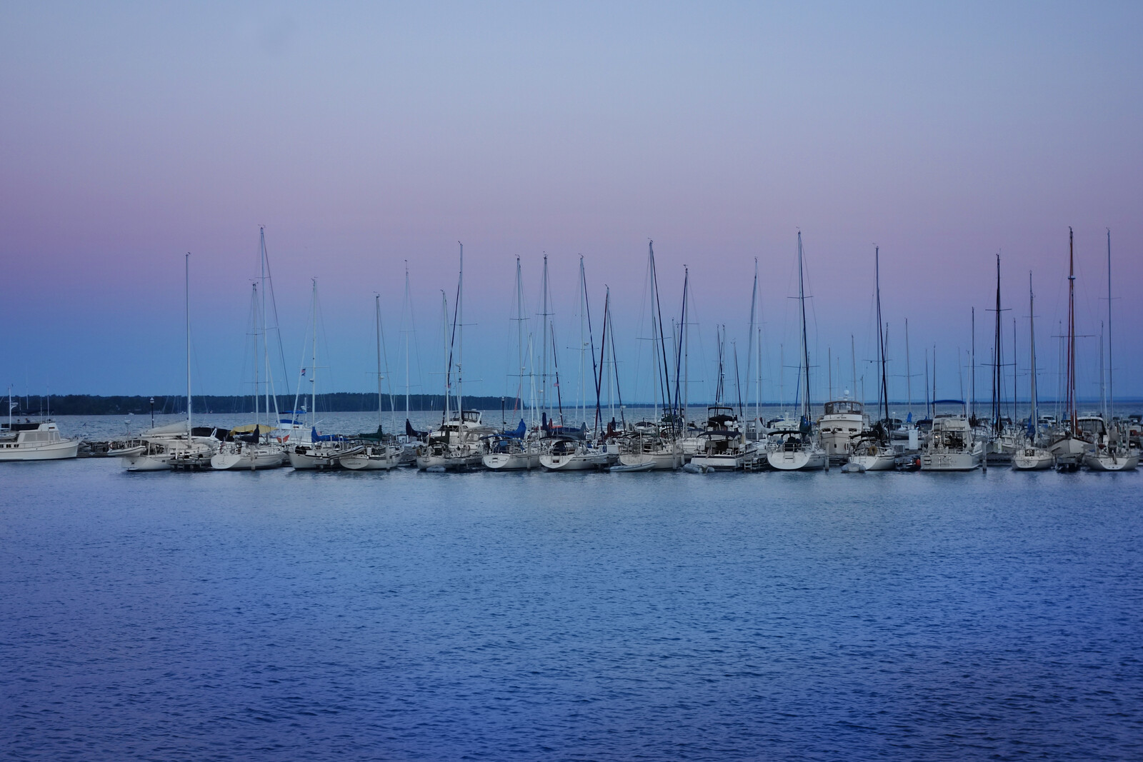 Sailboats in the marina in bayfield wisconsin at dusk, with lake superior and apostle islands in the background