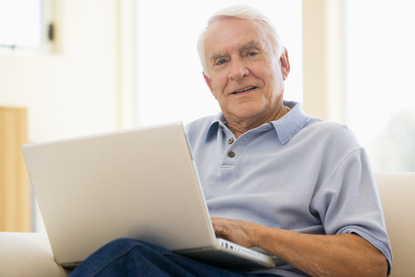 Senior man looking into the camera with a laptop on his lap sitting on  couch