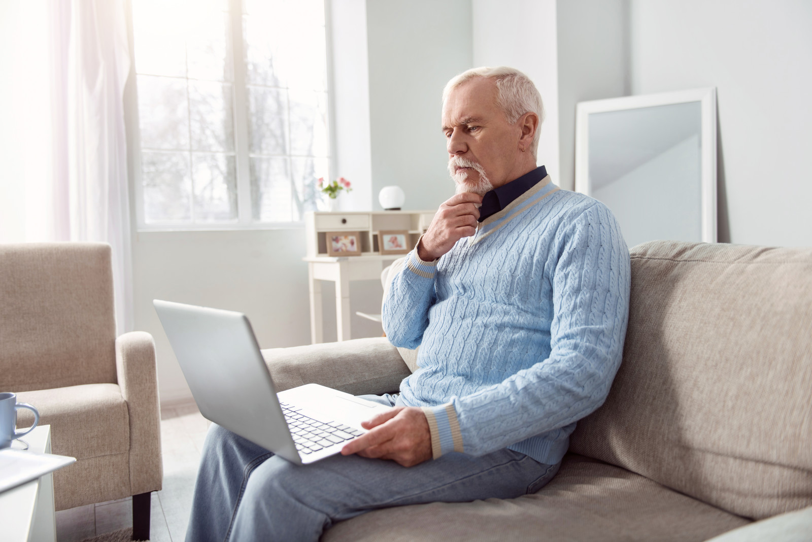Senior man sitting on the couch and reading from the laptop scratching his chin, with a concerned look on his face