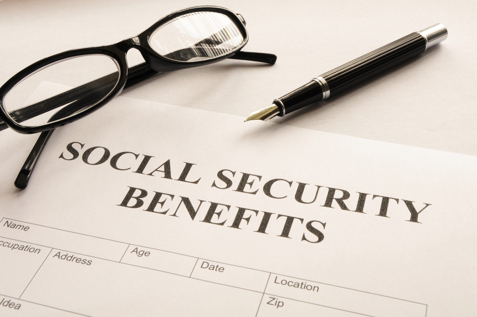 Don't be a Victim of Social Security Scams-Social Security Benefits paperwork with a black pen and reading glasses laying near the paperwork