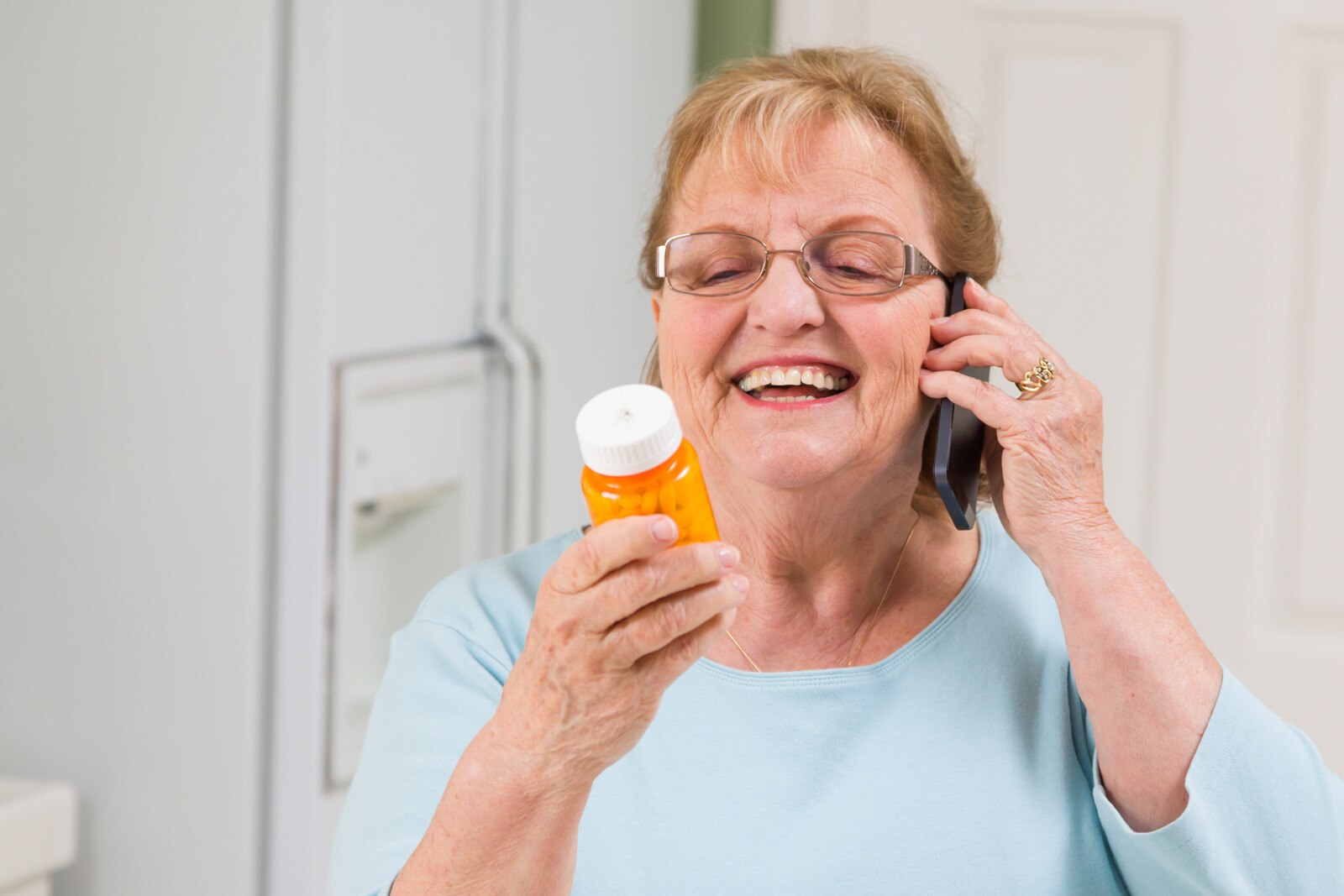 Smiling senior woman on the phone reading off a pill bottle