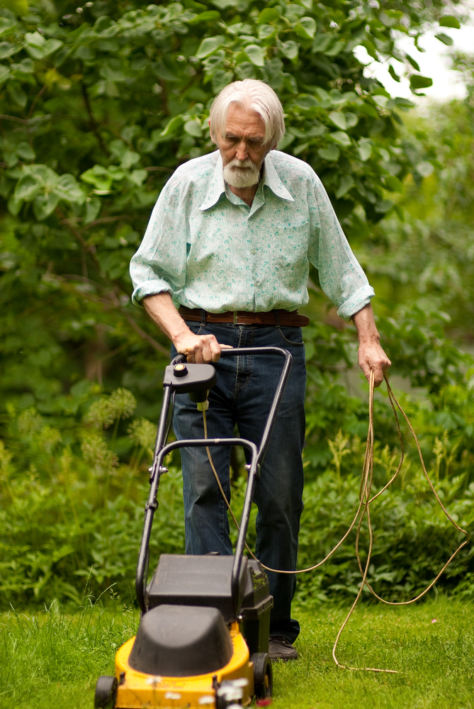 man with grey hair holding electric mower cord and pushing yellow mower