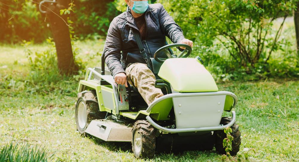 older man on green riding mower