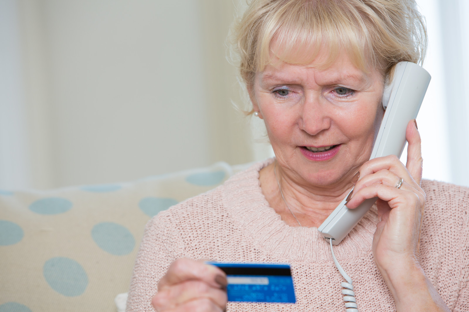 senior woman on phone with credit card in hand
