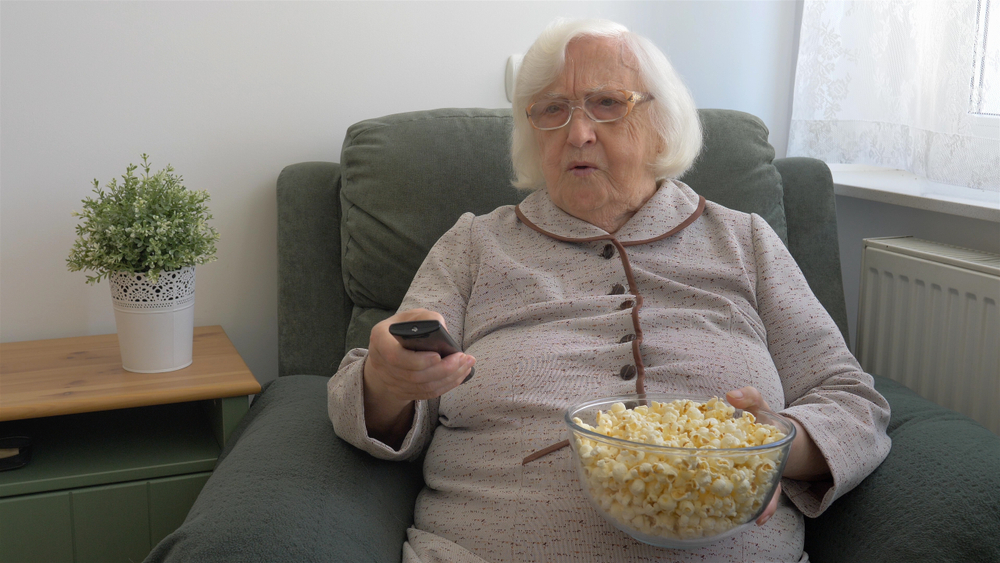 senior woman with popcorn bowl on cloth recliner