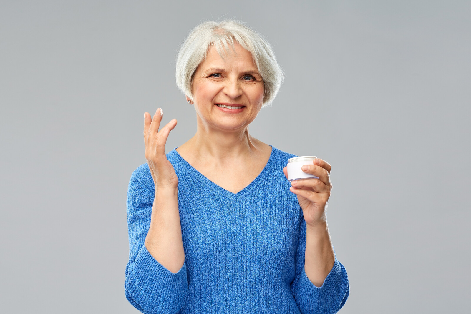Smiling senior woman holding a jar of anti-aging cream with some on her finger tips ready to apply