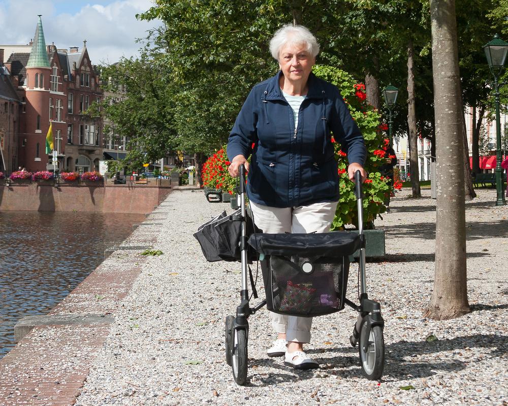 senior woman walking down European street with rollator walker no back rest