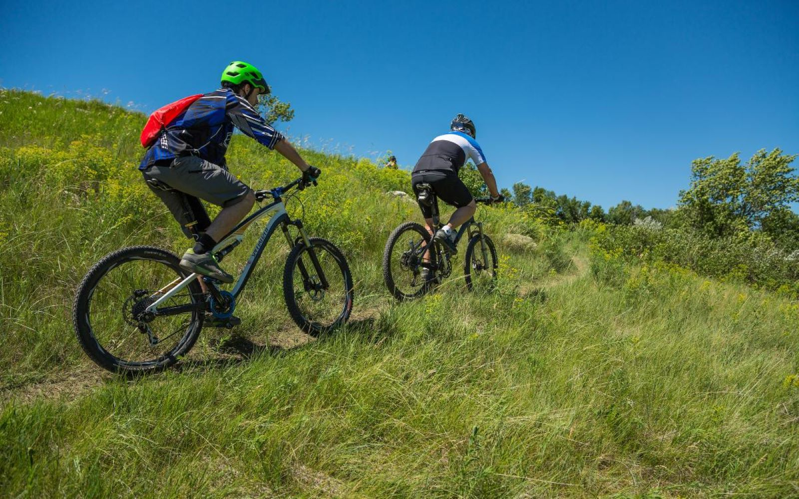 two people Mountain Biking up a grassy hill on a summer day in Jamestown ND with clear blue skies in the background