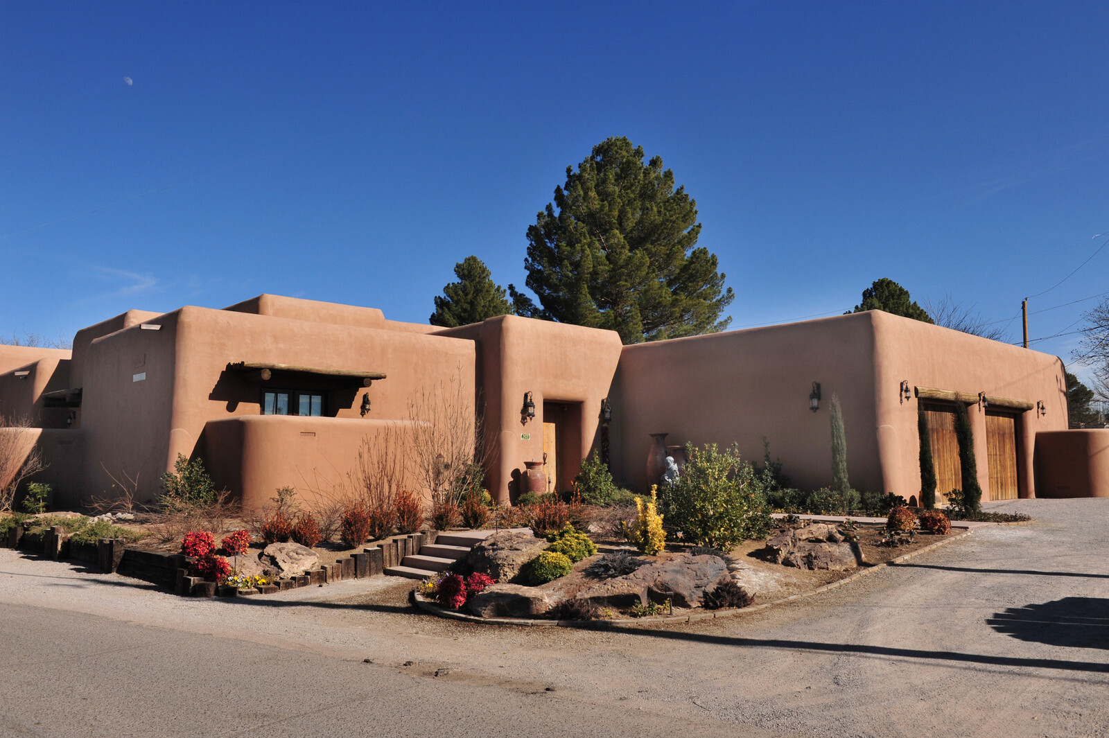 Adobe sytle home with a rock garden out front and wooden accents and garage doors