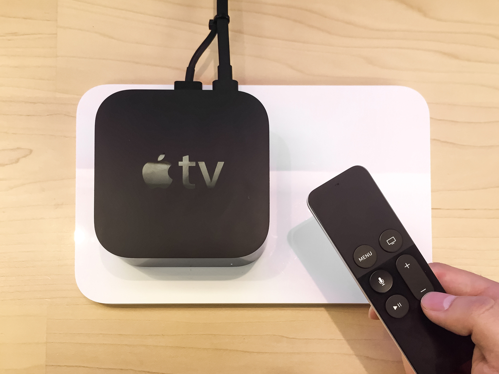 An Apple TV+ device and a hand holding a remote