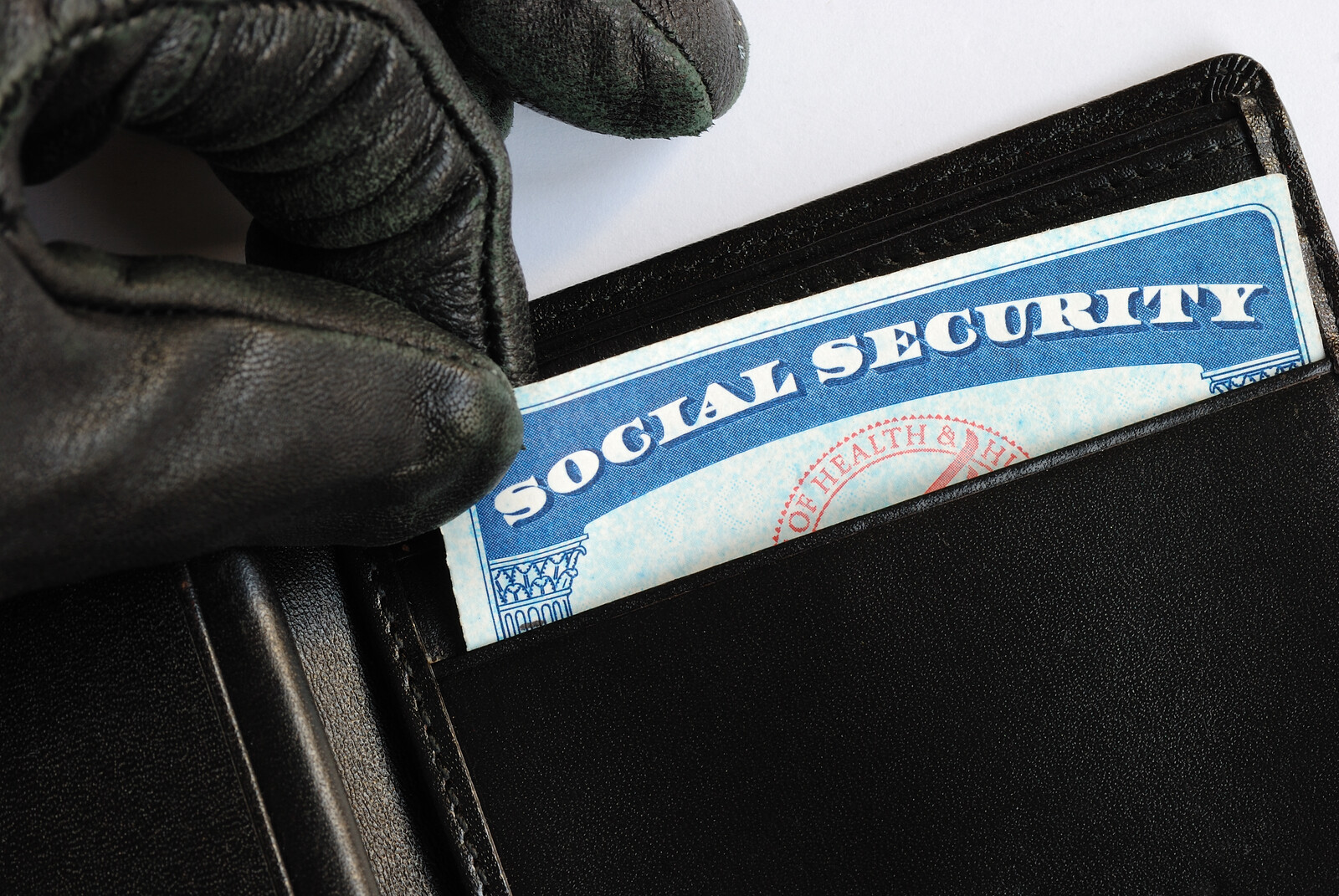 Black gloved hand pulling a social security card out of a wallet – representing identity theft