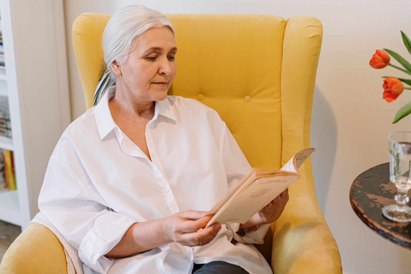 7 Ways Seniors Can Improve Brain Health Without Pills - Senior woman sitting in yellow chair reading a book
