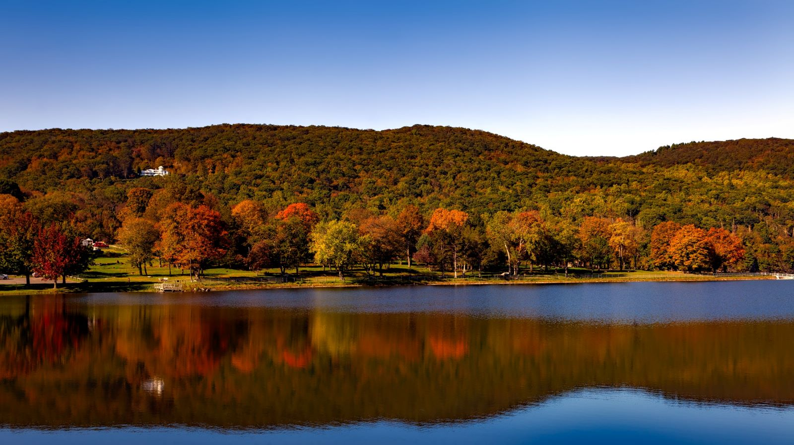 Best Places to Retire in Connecticut-Squantz pond state park in the fall, with still waters and the trees reflecting beautiful fall colors with blue sky