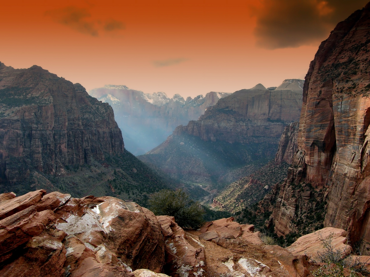 Places to Retire in Utah-zion state park at dusk orange skies, rocky moutains and rocks with beam of sunlight coming down into the valley
