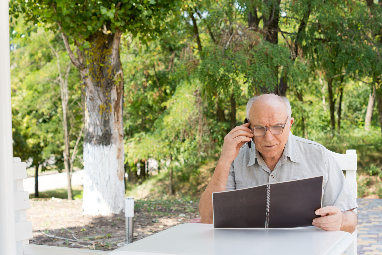 Senior man sitting outside at his table looking at a manual on his phone