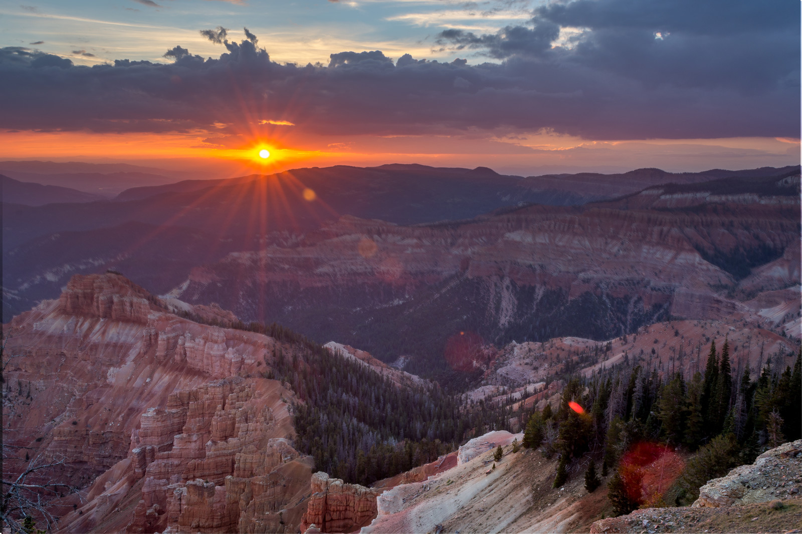 Sunset overlooking cedar breaks national monument with purple skies and evergreens coming down the hills in cedar city, ut.