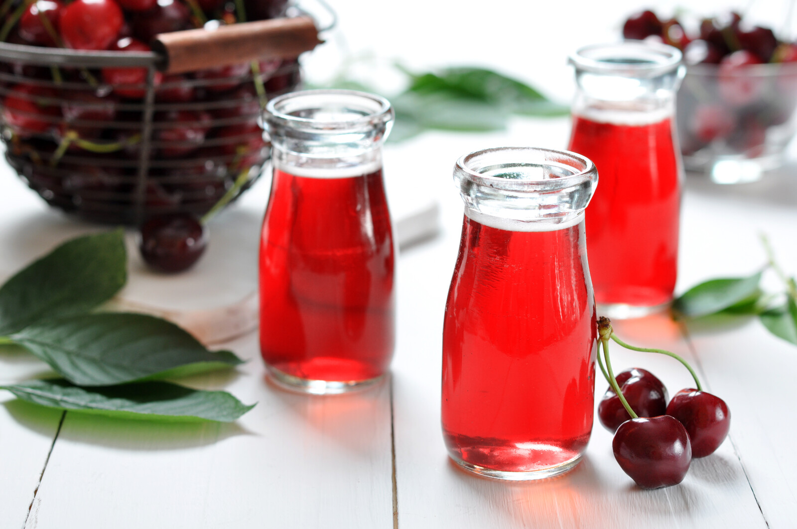Cherry juice in juice jars and fresh ripe cherries in baskets on wooden white table in the background