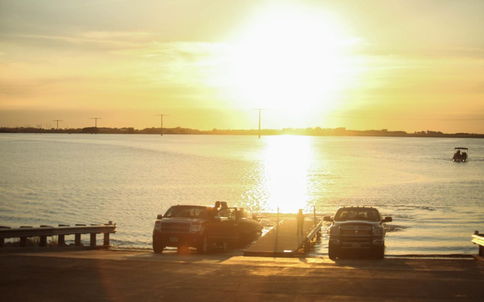 Golden Sunset reflecting off the water of Devils lake, a pontoon boat in the distance and two vehicles at the boat launch.