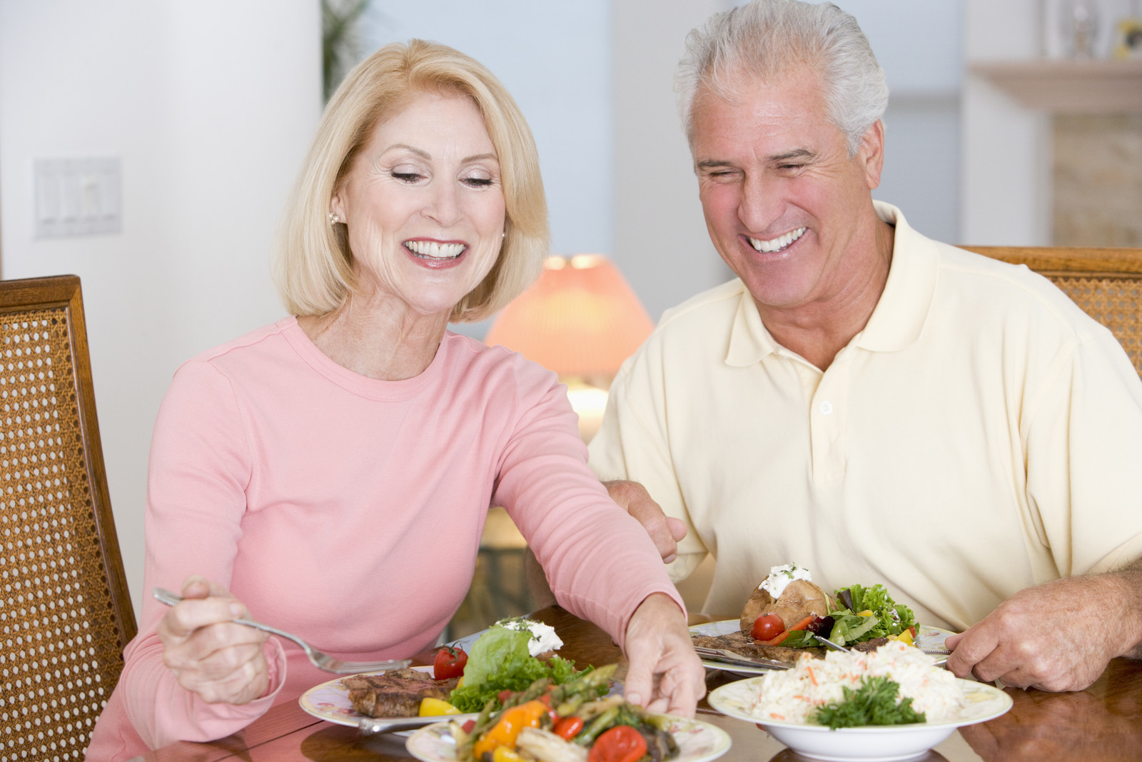 senior couple smiling and enjoying healthy meal at the dinner table