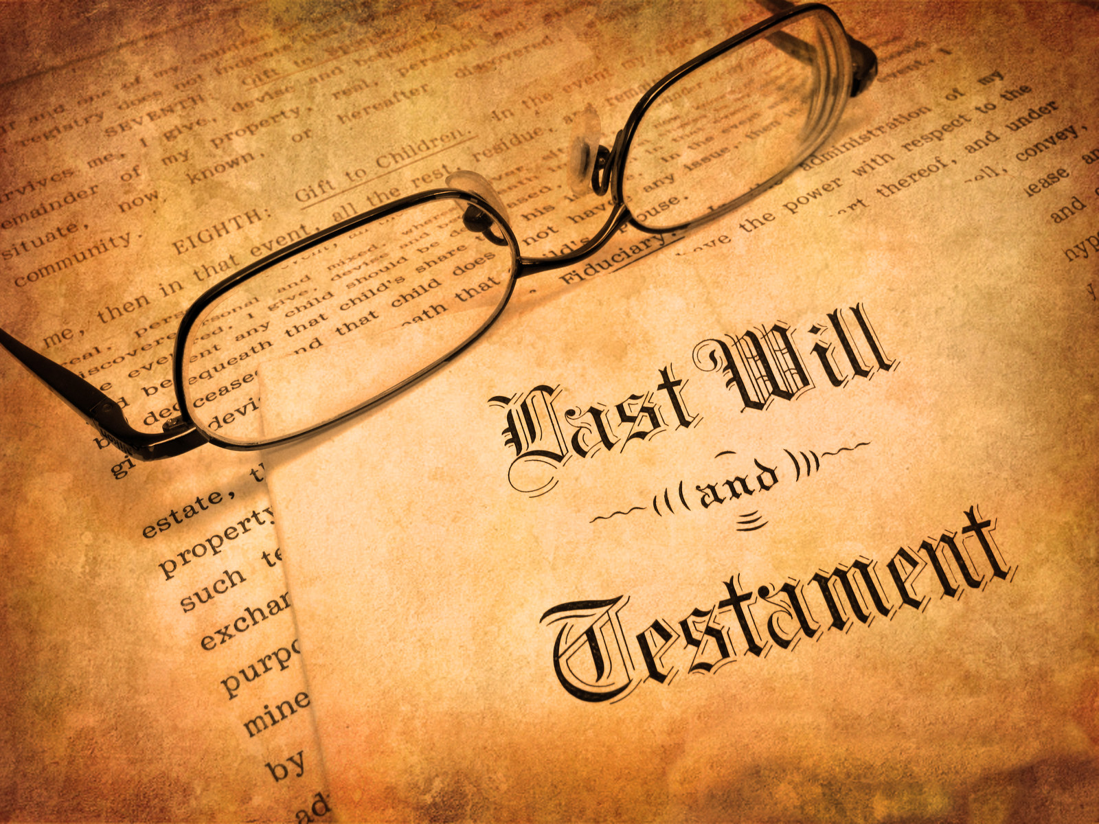 Aged paper and Envelope with last will and testament and reading glasses resting over the top of the papers