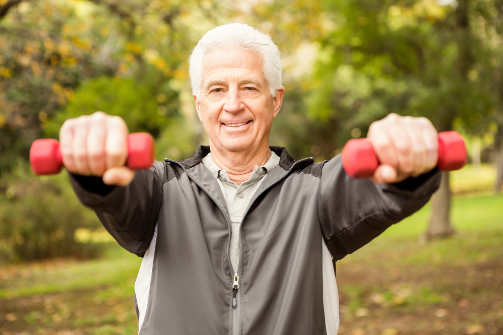 A senior man in a park exercising with weights
