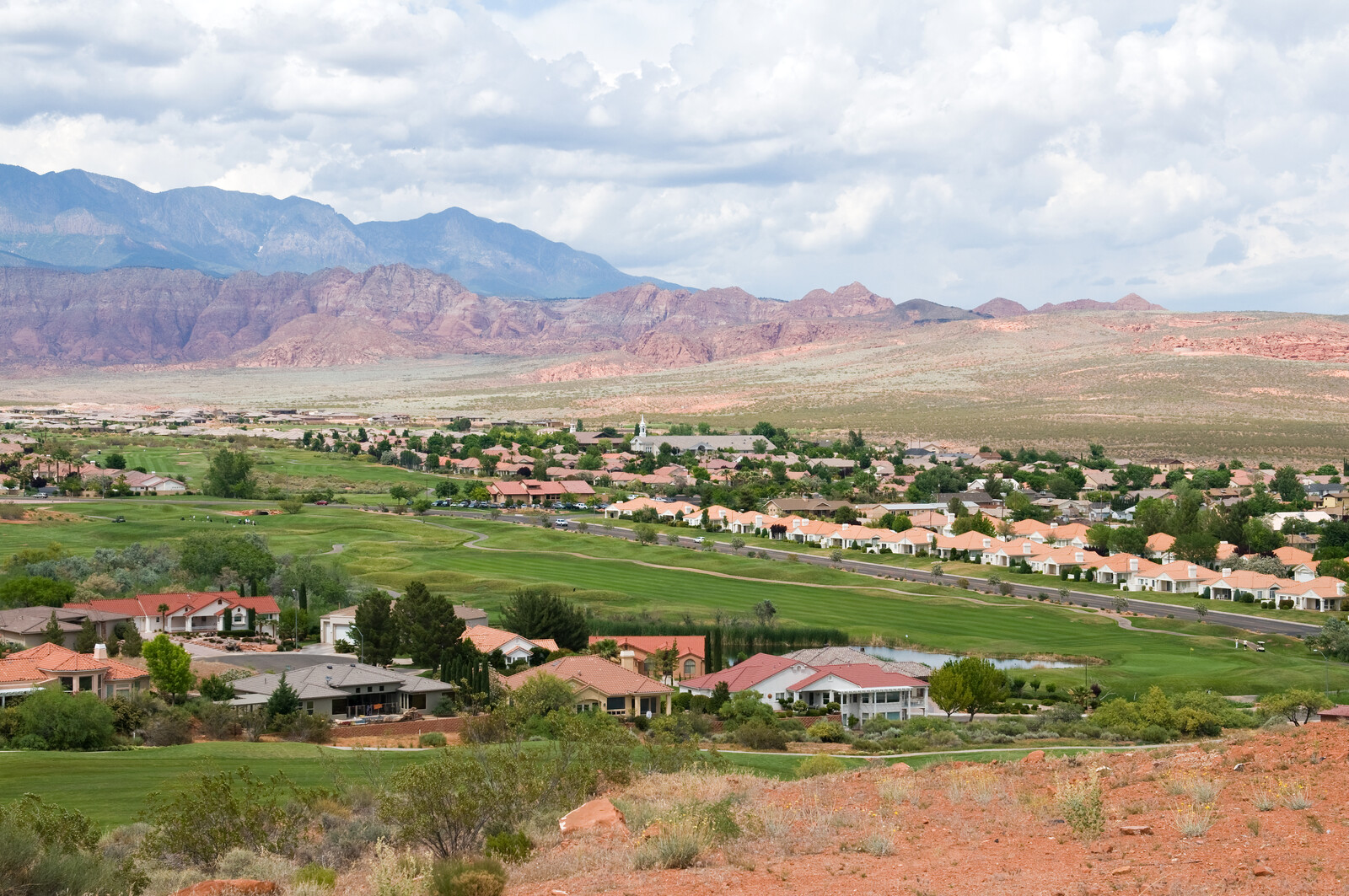 Housing development against red rocks in saint george, Utah, green grass around the houses, but scrub grass and rocky hills in the background