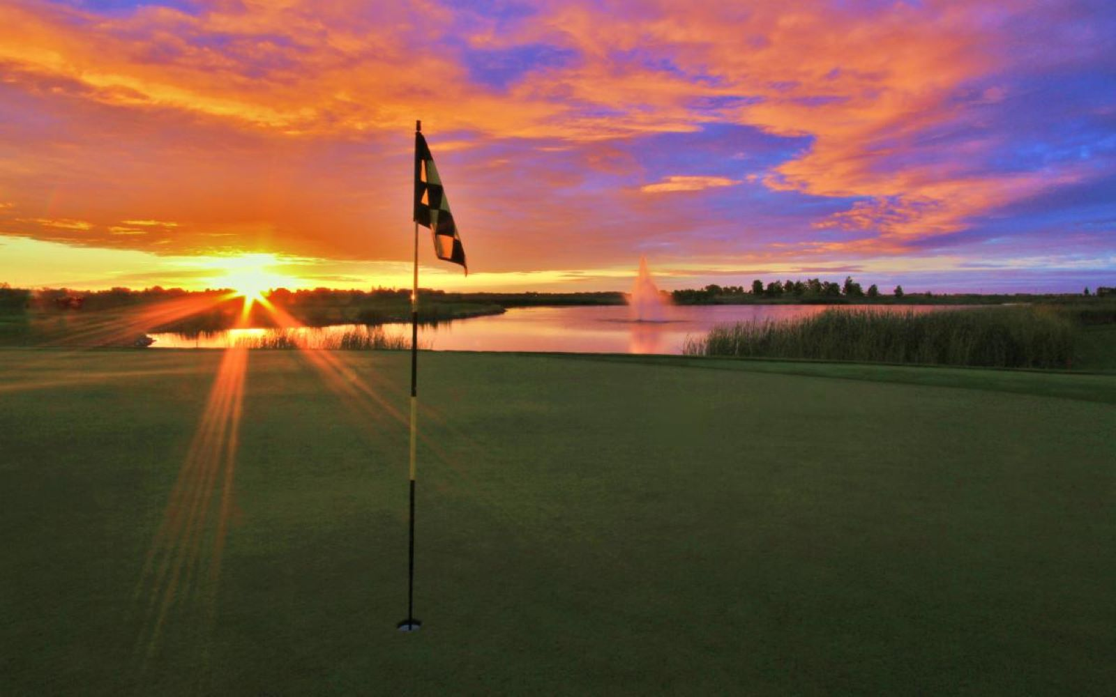 Sunrise on Hole nine at Kings Walk Golf Course in with a pond and fountain in the background at sunset, with a purple and pink sky back drop in Grand Forks North Dakota
