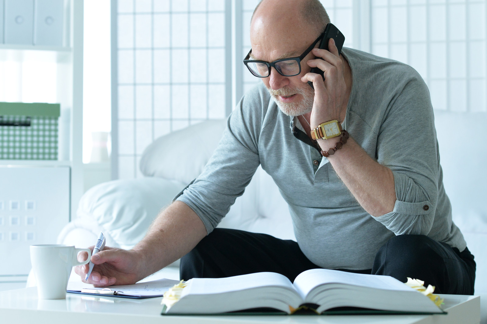 Mature man talking on the phone at home taking notes on a clipboard