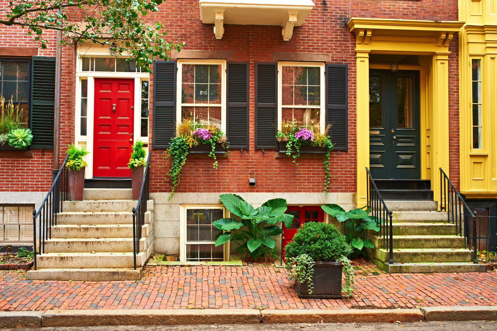 Cobblestone sidewalk in a small town neighborhood with colonial style townhouses, bright colored plants and flowers