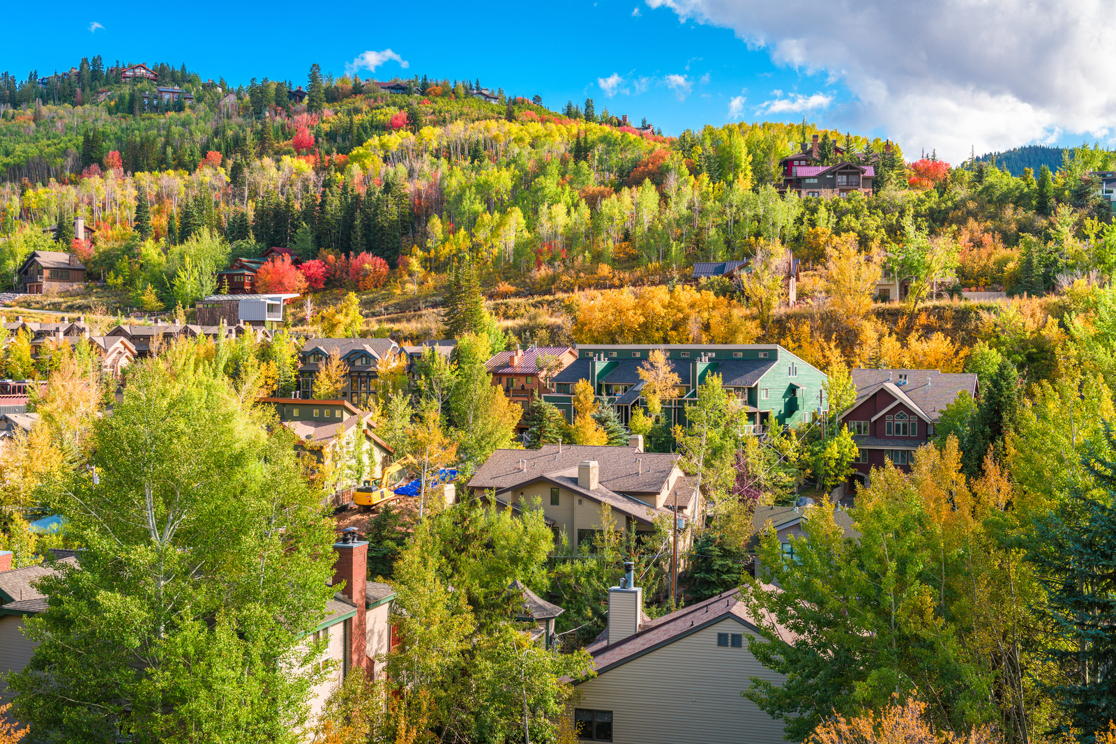 Housing scape along the hills amongst fall colored trees and blue skies