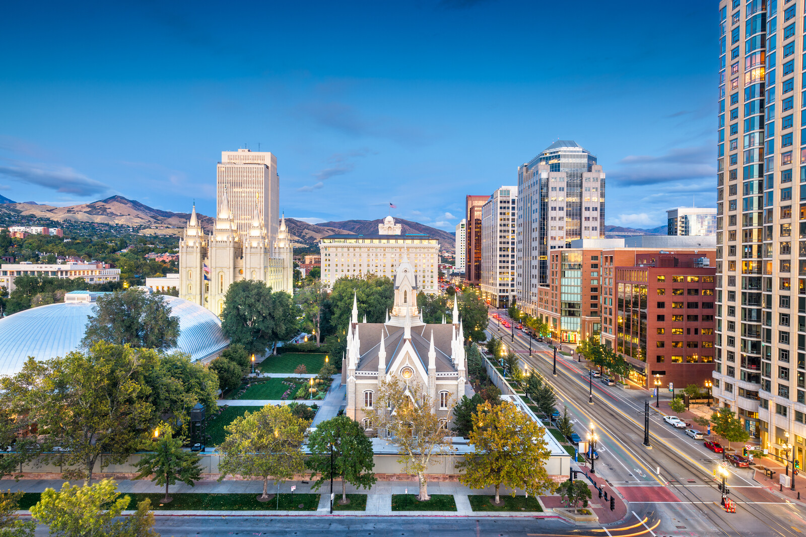 Salt lake city, utah, downtown cityscape over temple square at dusk with blue skies and precisely manicured greens and trees