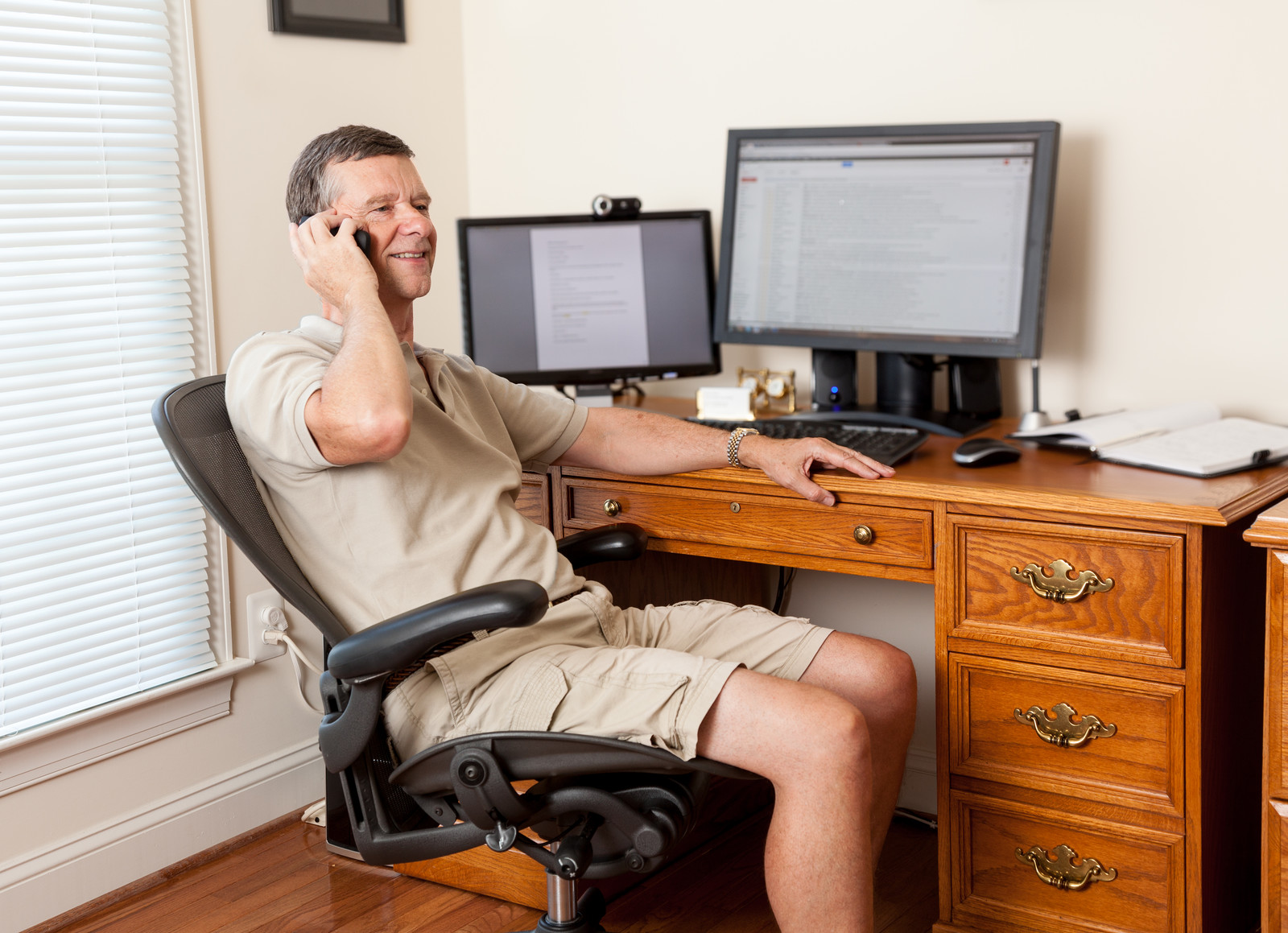 Senior man sitting at home at desk with two monitors smiling while talking on the phone