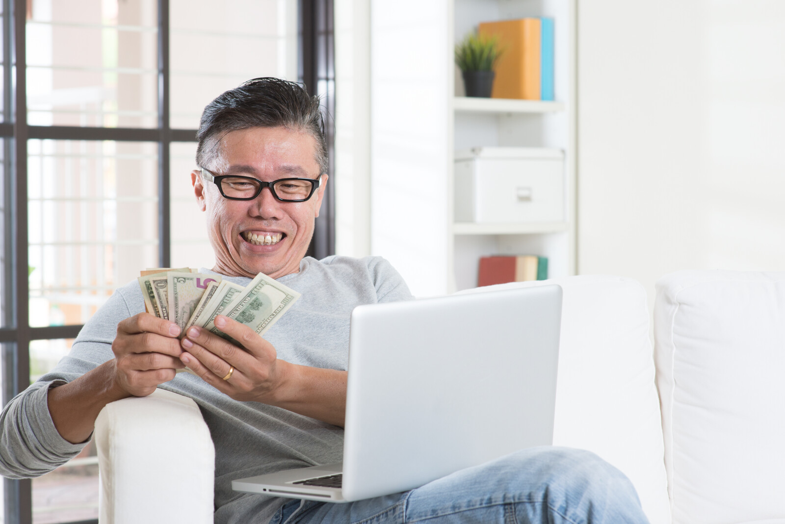 Work-From-Home Scams Targeting Seniors - Man counting cash smiling while sitting on the couch with his lap top