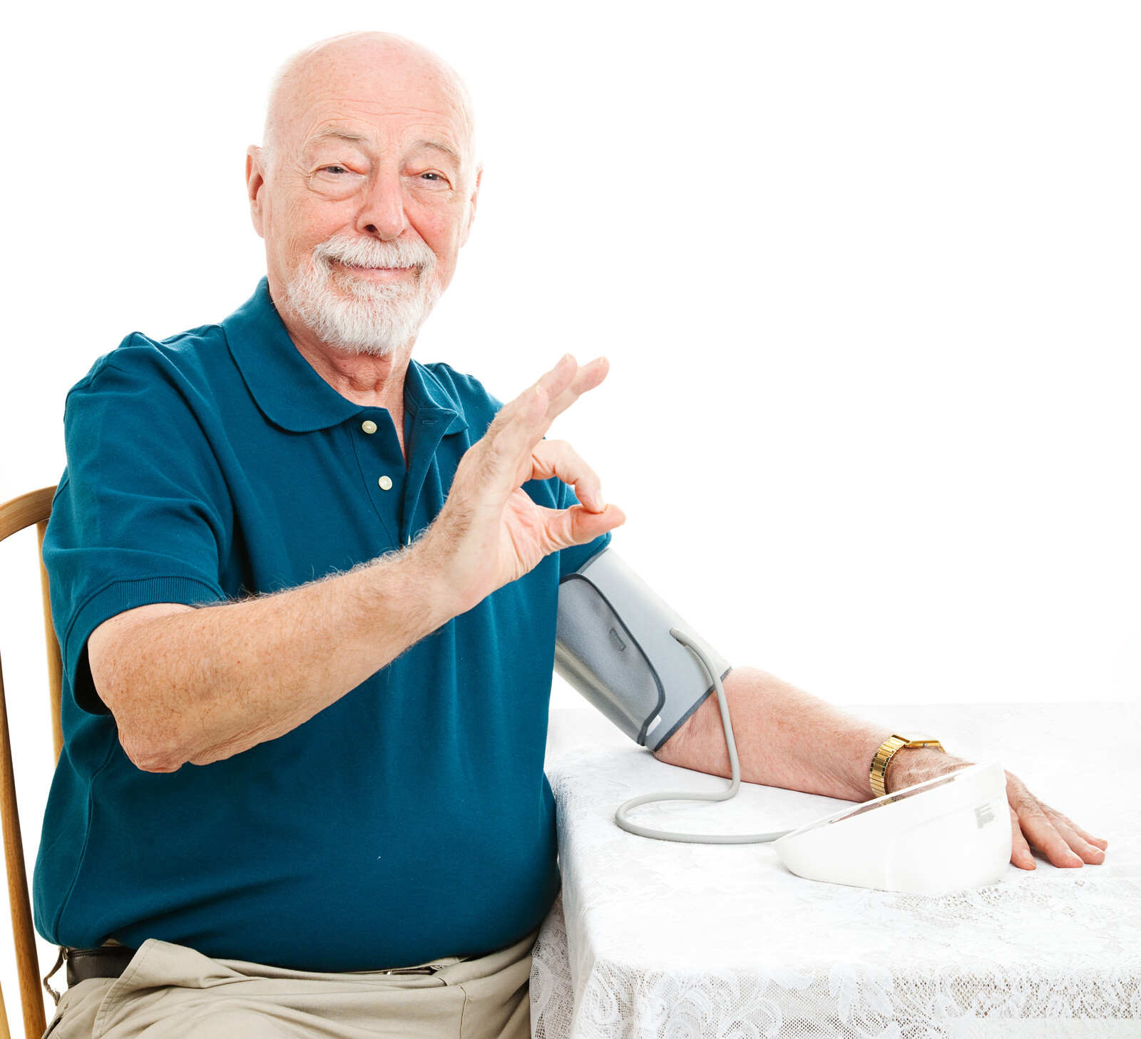 Senior man taking his blood pressure at kitchen table and giving okay hand sign.