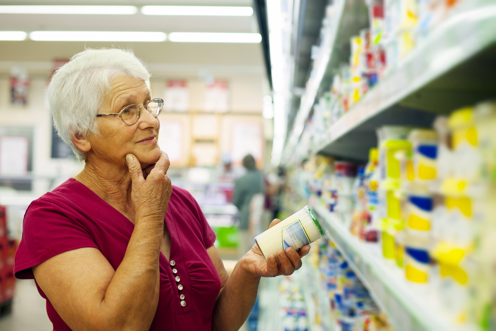 Senior woman pondering options at a grocery store