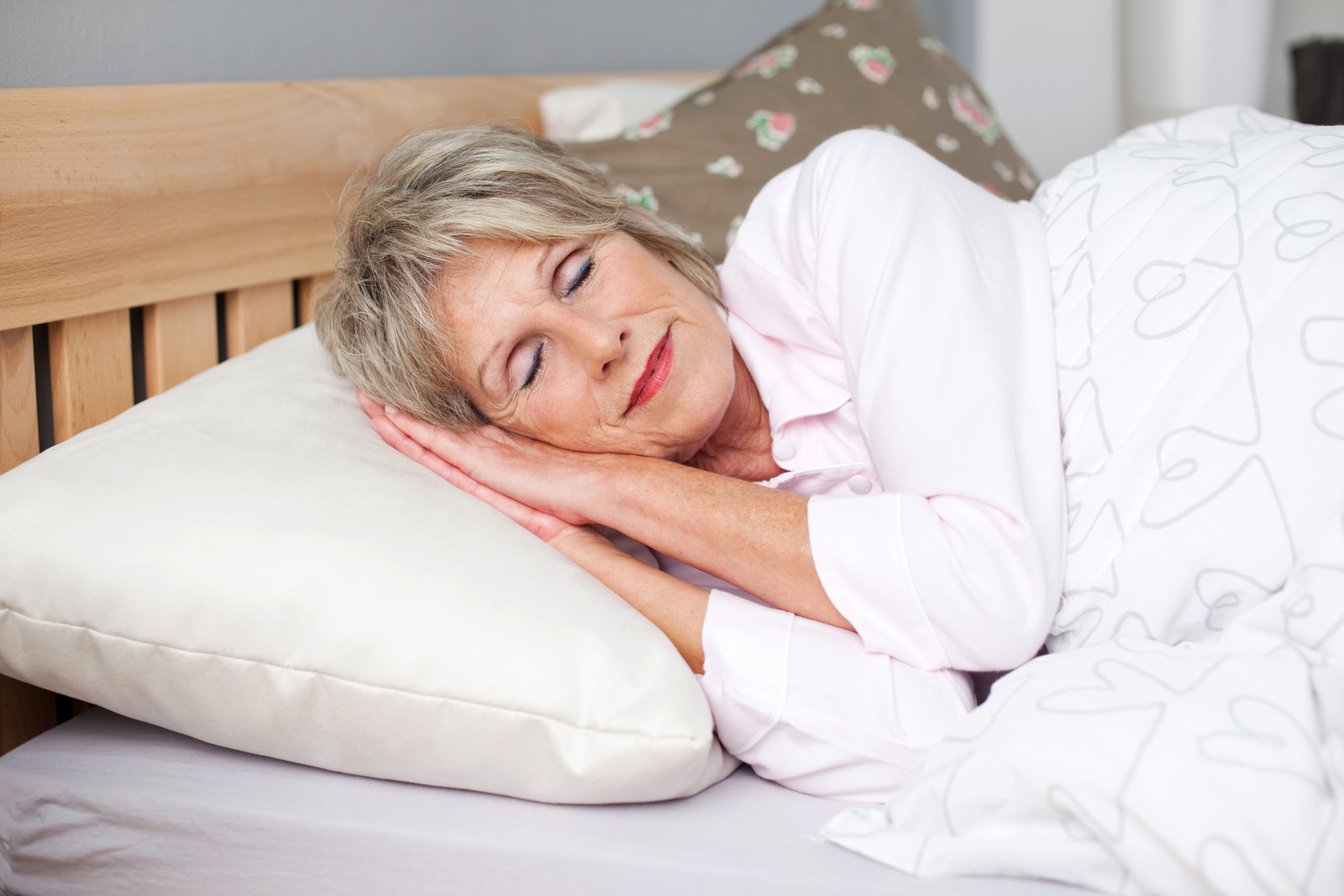 Top 7 Natural Sleep Supplements For Seniors -Smiling senior woman sleeping soundly in bed
