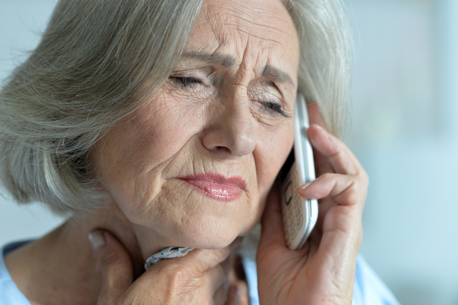 Senior woman talking on the phone looking distressed holding a kerchief